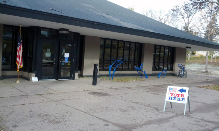 Photo outside polling place with sign reading, 'vote here' with arrow pointing to door